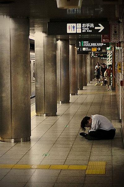 Спящие жители Токио на улицах города